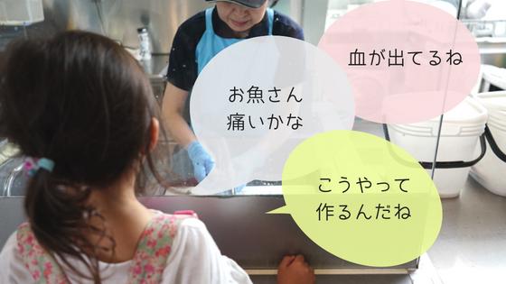 魚の調理を見る子ども
